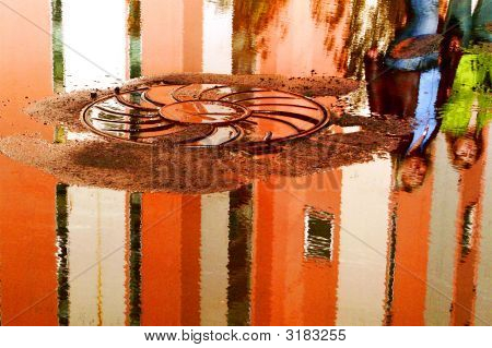 City. Reflection In Puddle