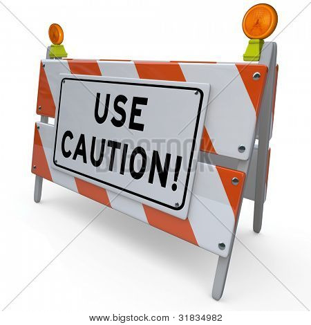 An orange and white construction barricade sign telling you to Use Caution when entering a dangerous area and warning you to be careful to avoid hazards