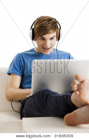 Young man sitting on the couch and listen podcast over the internet