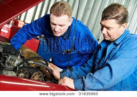 two motor mechanic engineers examining timing belt and internal combustion engine of automobile car at repair service station