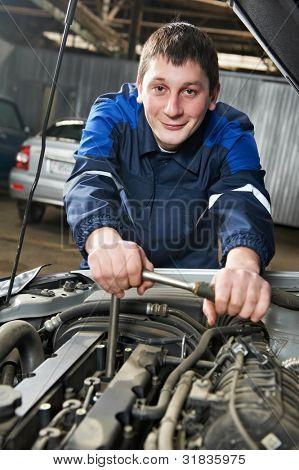 Sorrindo feliz mecânico automotivo aperte o parafuso com uma chave durante a manutenção do automóvel carro no en