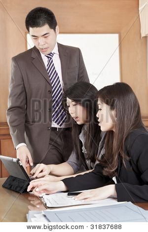 Manager helping his subordinate in the office