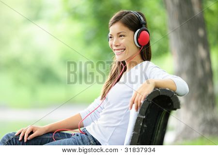 Woman listening to music in park wearing headphones smiling happy. Mixed race Asian Caucasian young woman relaxing outdoors enjoying spring.