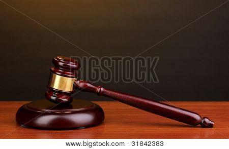 Martelo de juiz na mesa de madeira no fundo marrom