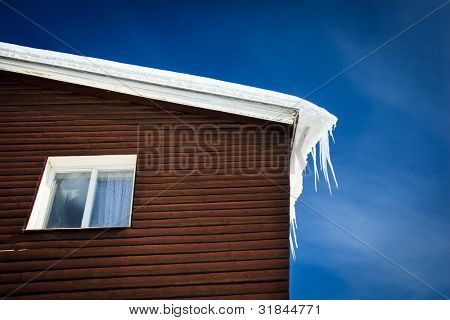 Winter/mountain concept: closeup of a wooden cottage roof covered with snow and icicles against blue sky