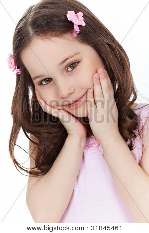 Vertical shot of a cute little girl smiling and posing in front of the camera