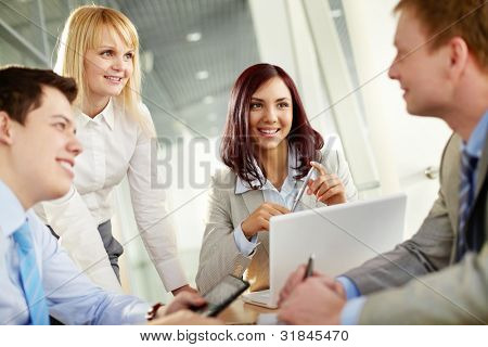Business people looking at their male colleague approvingly as he has come up with a really good idea