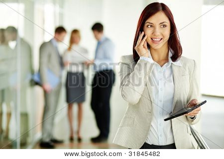 Business lady answering the phone with a smile, receiving good news