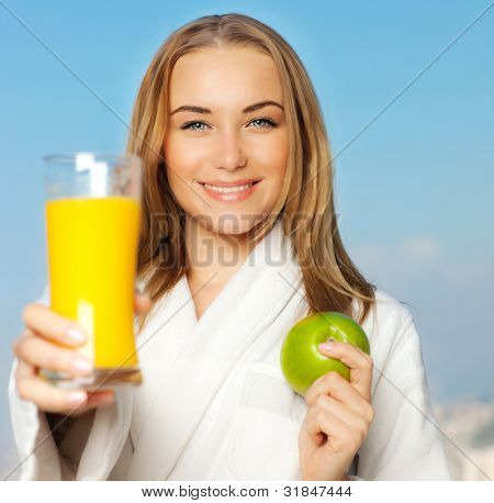 Healthy lovely young woman dieting, beautiful girl holding orange juice and green fresh apple fruit, happy smiling female portrait outdoor over blue sky background, nutrition and wellness concept