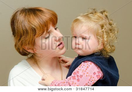 Close Up Of Affectionate Mother And Daughter on brown background.