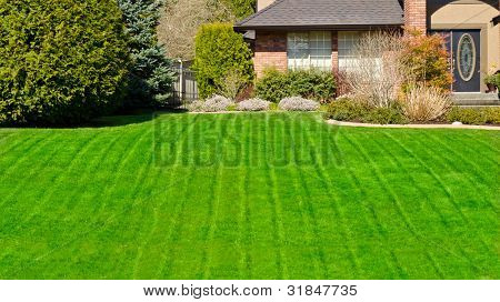 Fragment of a nice house with gorgeous lawn and outdoor landscape in Vancouver, Canada.