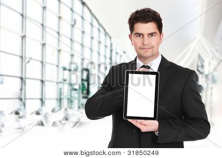 A portrait of a young businessman standing over the background of his modern office and presenting your product on tablet's screen