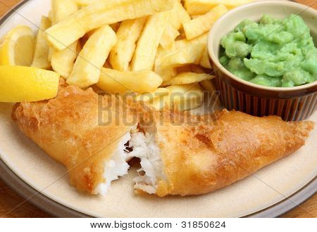 Fried cod fillet with chips and mushy peas. Shallow DoF, focus on the fish.