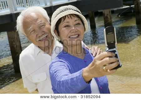 Couple Taking Their Own Photograph with Camera Phone
