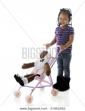 A happy preschooler stopping to pose with the doll she's pushing in an umbrella stroller.  On a white background.