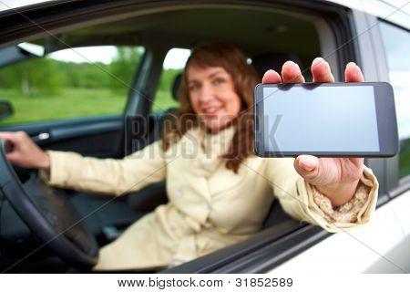 Hermosa mujer sentada en un coche y mostrando su smartphone a través de la ventana