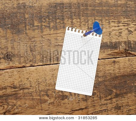 dart in blank notepad on a vintage wooden board