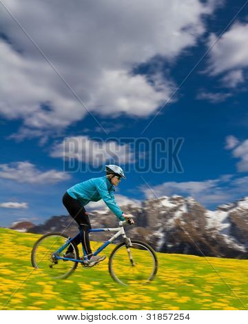 Mountain biking down - woman downhill on bike in dandelion, snowy Dolomites mountain  in the background