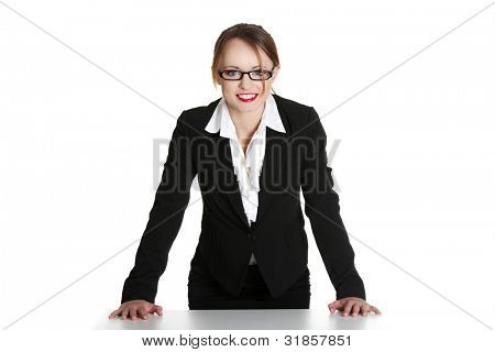 Portrait of beautiful successful businesswoman standing behind the desk. Isolated on white