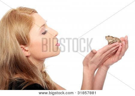 A gorgeous young blond woman kissing a frog , isolated on white