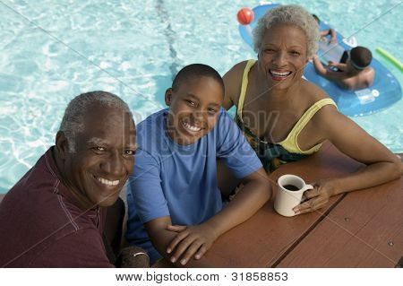 Grandparents and Grandson Sitting Poolside