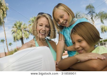 Girls and Grandmother Watching TV at Pool