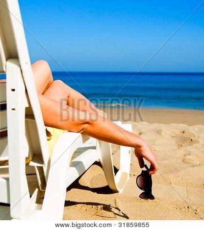 Mädchen auf einem Strand Liege mit Brille in der hand liegend
