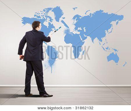 Empresário com mapa de escova e mundo de pintura sobre o fundo