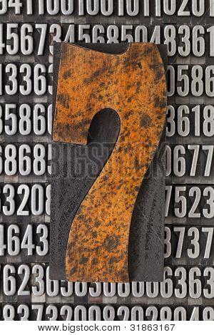 number seven in vintage letterpress wood type against background of random metal numbers