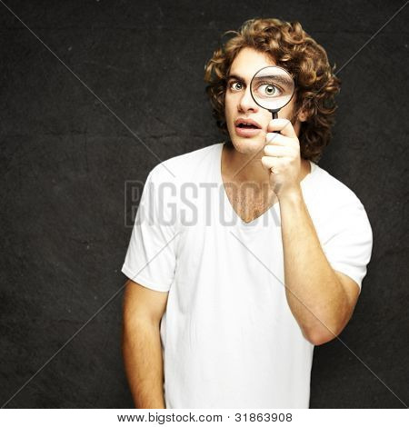 portrait of young man looking through a magnifying glass against a grunge wall