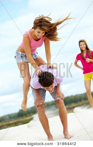 Vertical shot of a girl jumping over her friend�?�¢??s back, vivid an dynamic photo
