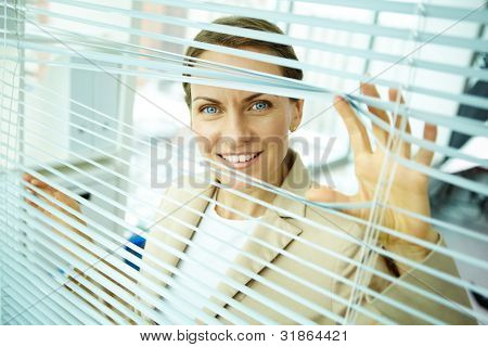 Confident business woman sliding apart blinds to see better what is going outside