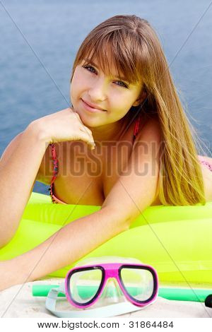 Pretty teenage girl lying on an air bed and looking at camera with a smile
