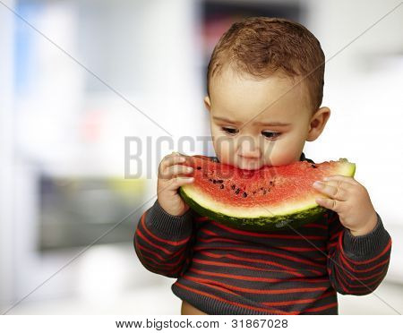 portrait of a handsome kid holding a watermelon piece
