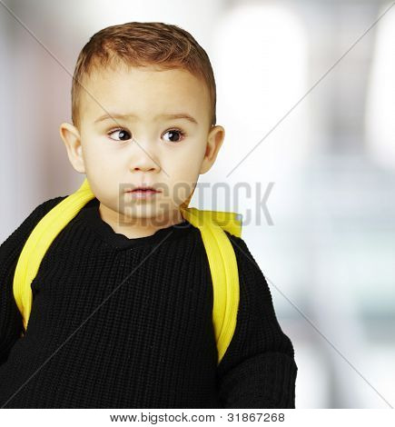 portrait of adorable kid carrying yellow backpack indoor