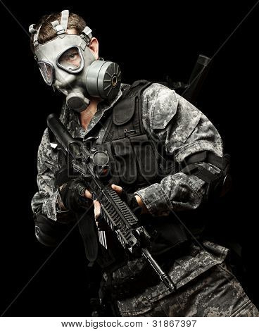 portrait of young soldier with gas mask and rifle against a black background