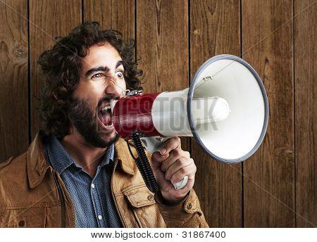 retrato de jovem gritando com megafone contra uma parede de madeira