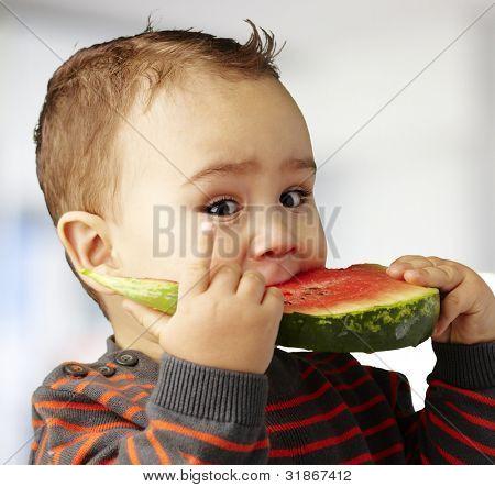 portrait of a handsome kid biting a watermelon piece indoor