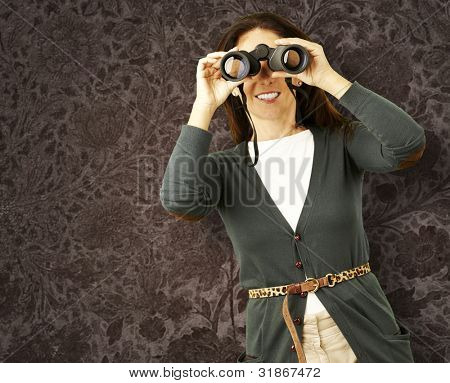 portrait of middle aged woman looking with binoculars against a vintage wall