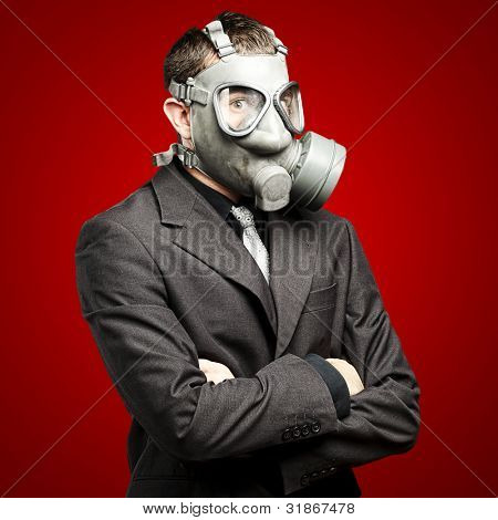 portrait of a business man with gas mask over red background
