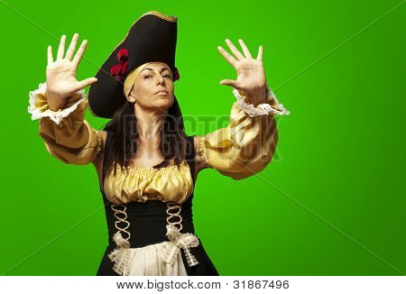 portrait of pirate woman gesturing stop against a green background