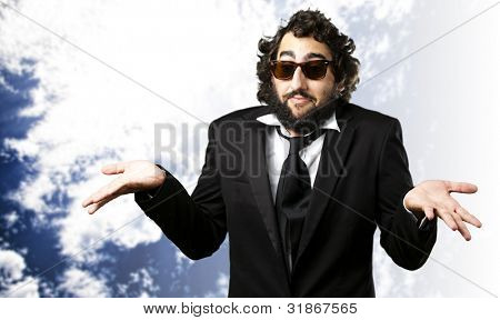 portrait of young business man confused against a cloudy sky background