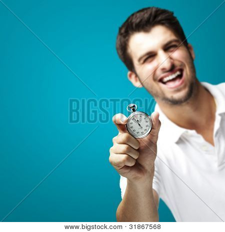 portrait of young man holding a stopwatch against a blue background