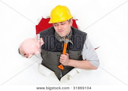 Laborer holding hammer and piggy bank
