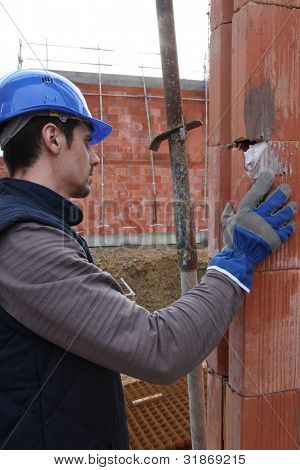 Bricklayer checking brick wall