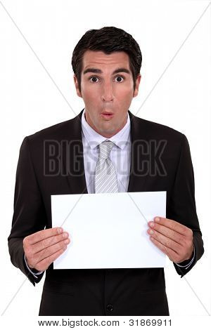 Surprised businessman with a blank board