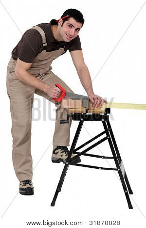 Male carpenter sawing.