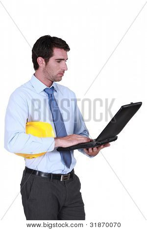 Architect stood typing on laptop