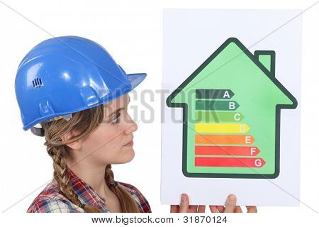 Female housebuilder with an energy rating sign