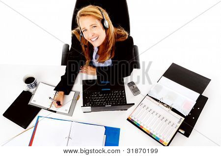 Business woman working at her desk, happy and smiling as she multitasks